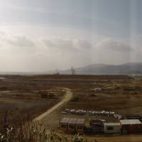 Work is underway Feb. 24 to raise the land of a low-lying coastal neighborhood by about 10 meters in Rikuzentakata, Iwate Prefecture, where the tsunami of March 11, 2011, destroyed 4,045 dwellings. | SHUSUKE MURAI