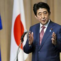 Prime Minister Shinzo Abe addresses a symposium Monday at United Nations University in Tokyo. | KYODO