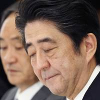 Prime Minister Shinzo Abe bites his lips during a meeting with a panel of experts at his official residence in Tokyo on Feb. 25. Behind Abe is Chief Cabinet Secretary Yoshihide Suga.   AP
