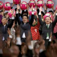 Prime Minister Shinzo Abe (center) and fellow members of his Liberal Democratic Party shout the traditional banzai cry while lofting Daruma dolls at the party's annual convention in Tokyo on Sunday. | AP