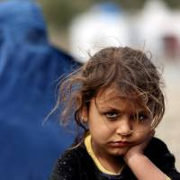 An Afghan refugee is shown following her arrival at the International Organization for Migration office in Torkham, an Afghan town that borders Pakistan, on March 11. | AP