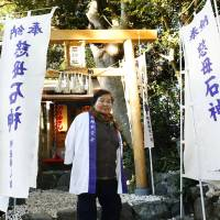 Shigako Imura, a retired female diver, poses in front of a small Shinto shrine in Toba, Mie Prefecture, after paying her respects on Dec. 9. Known locally as Ishigami-san, the shrine in the city's Osatsu area is believed to protect female divers who have supported the local economy. | KYODO