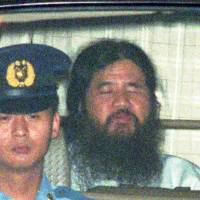 Aum founder Shoko Asahara is driven from the Tokyo District Court on July 7, 1995, after a 10-day extension of his detention was approved.   AP