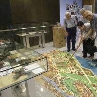 Visitors look at a map during a commemorative event for the 70th anniversary of the Battle of Manila at Ayala Museum in suburban Makati, south of Manila, on Feb. 3. | AP