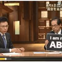 Shigeaki Koga (right), a former government bureaucrat critical of Prime Minister Shinzo Abe, holds up a sign in this screenshot of his appearance on a news program aired by TV Asahi on Friday.