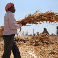 A farmer and his wife work in a field in front of a coal-fired power plant, partially financed by the Japan Bank for International Cooperation, under construction in Kudgi, India, in February. Despite mounting protests, Japan is continuing to finance projects underway in India and Bangladesh with money earmarked to fight climate change. | AP