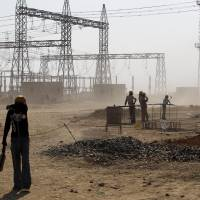 A worker shields himself from dust at a coal-fired power plant in Kudgi, India, being built with 'climate funding' from the Japan Bank for International Cooperation, on Feb. 24. JBIC agreed in January 2014 to provide $210 million in loans to Indian utility NTPC Ltd. to buy equipment from a local Toshiba Corp. subsidiary. | AP