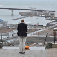 Britain's Prince William offers a silent prayer for the victims of the March 11, 2011, earthquake and tsunami as he looks over land raked by the tsunami from a hilltop in Ishinomaki, Miyagi Prefecture, on March 1. | AFP-JIJI