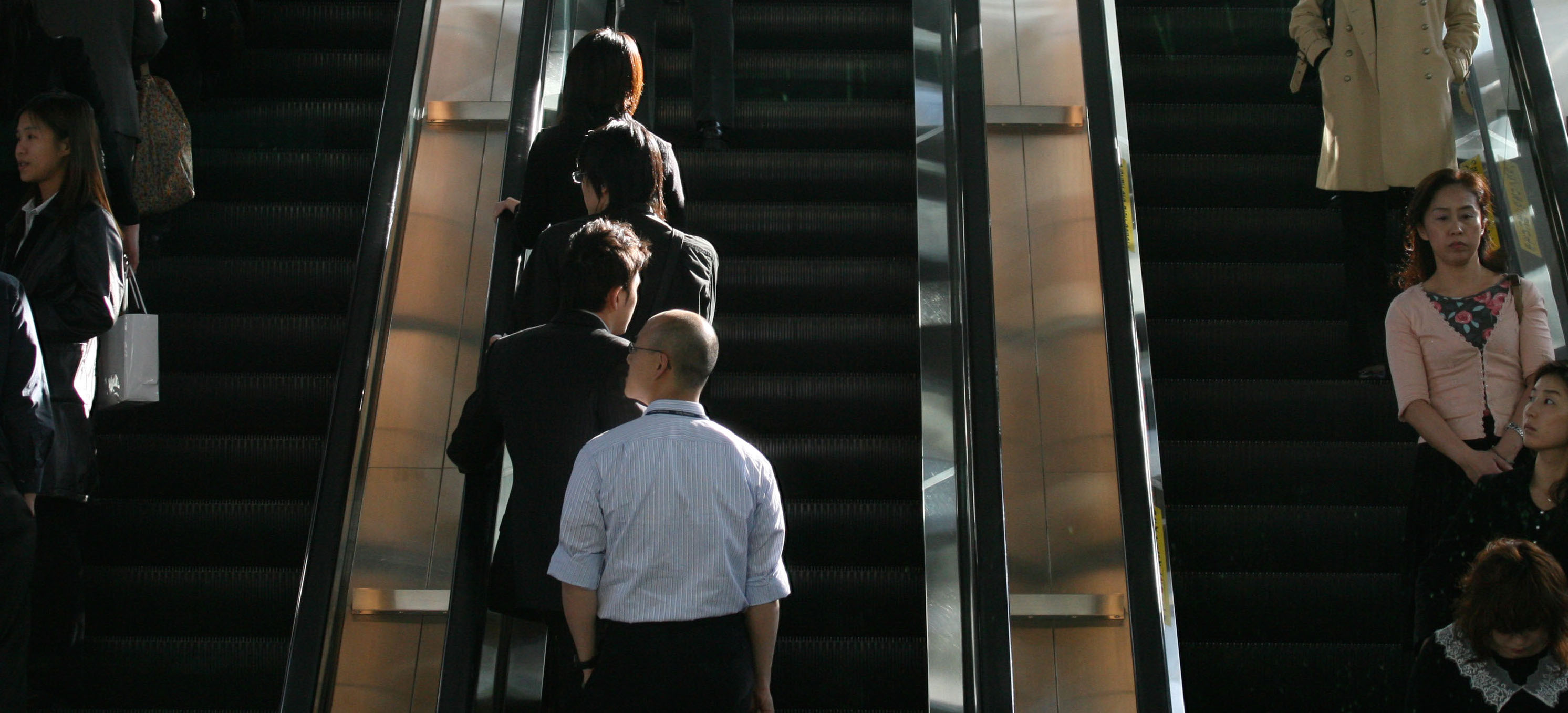 Commuters stand on the left of escalators in Tokyo. Osakans use the right-hand side, but an ordinance now under consideration would force them to change. | BLOOMBERG