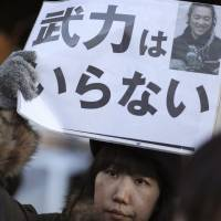 A protester outside Prime Minister Shinzo Abe's office on Feb. 1 holds a sign reading 'We do not need armed forces,' after Islamic State extremists executed journalist Kenji Goto. | AP