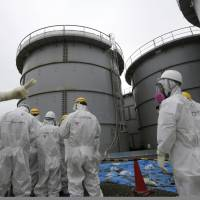 A Tokyo Electric Power Co. official briefs journalists in protective suits at the Fukushima No. 1 nuclear plant in November 2013. | AP