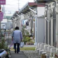 A resident walks through a temporary housing complex in Koriyama, Fukushima Prefecture, in November. | KYODO