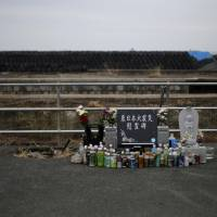 A monument and a stone statue of Jizo for victims of the March 11, 2011, earthquake and tsunami are seen near big black plastic bags containing radioactive soil, leaves and debris from the decontamination operation at a temporary storage site in Tomioka, Fukushima Prefecture, near Tokyo Electric Power Co's tsunami-crippled Fukushima No. 1 nuclear power plant on Feb. 22. Many residents of Okuma, a village near the plant, are angry about government plans to dump some 30 million tons of radioactive debris raked up from th disaster in a sprawling waste complex on their doorstep. Few believe Tokyo's assurances that the site will be cleaned up and shut down after 30 years. | REUTERS