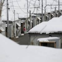 A woman is seen at a temporary housing complex that accommodates nuclear evacuees from Okuma, a town inside the exclusion zone next to Tokyo Electric Power Co's tsunami-crippled Fukushima No. 1 nuclear power plant, in Aizuwakamatsu, Fukushima Prefecture, Feb. 17. | REUTERS