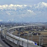 A new bullet train makes a trial run against the backdrop of the snow-covered Tateyama mountain range in Toyama Prefecture on Jan. 14 ahead of the opening of the Hokuriku Shinkansen Line on March 14. | KYODO