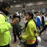 A member of the support staff for Tokyo Marathon 2015 communicates with a foreign participant using a translation application on his smartphone on Feb. 22.  | TOKYO MARATHON FOUNDATION