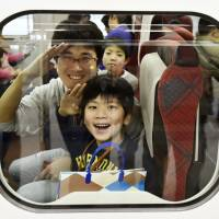 A father and his son salute through the window of a new bullet train at JR Kanazawa Station on Feb. 7, during a test ride on the Hokuriku Shinkansen Line. The train service, set to debut March 14, will connect Kanazawa and Tokyo via Nagano. | KYODO
