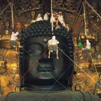 Priests dust the Great Buddha at Todaiji Temple, Nara Prefecture, in August. A giant baseball glove is in the making for the Buddha, as part of efforts to cheer up children in Tohoku, which was devastated by the March 2011 disasters.   KYODO