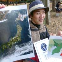 Yasushi Takahashi holds one of his GPS drawings in Saitama Prefecture, in a recent photo. The 37-year-old artist uses a GPS tracker to create images like the 'Marry me' message he used to propose to his girlfriend in 2008.   KYODO