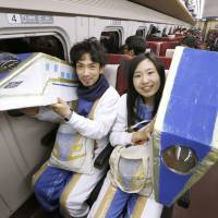 A couple in costumes pose on the first Kagayaki bullet train to depart from JR Kanazawa Station bound for Tokyo on Saturday morning after the Hokuriku Shinkansen Line opened for business. | KYODO