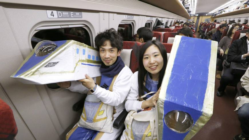 A couple in costumes pose on the first Kagayaki bullet train to depart from JR Kanazawa Station bound for Tokyo on Saturday morning after the Hokuriku Shinkansen Line opened for business.
