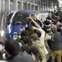 A crowd at JR Kanazawa Station snaps shots of a Kagayaki bullet train Saturday as it arrives from Tokyo, following the launch of the Hokuriku Shinkansen Line. | KYODO