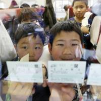 Children riding a Kagayaki bullet train show off their tickets Saturday morning at JR Nagano Station after the Hokuriku Shinkansen Line opened for business. | KYODO
