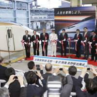 Bureaucrats and officials perform a ribbon-cutting ceremony on a platform at JR Nagano Station on Saturday to mark the opening of the Hokuriku Shinkansen Line. | KYODO
