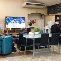 People sit in January in the lobby of an Osaka hotel refurbished from what used to be quarters for day laborers, amid a surge in travelers from overseas. The hotel offers a Wi-Fi Internet connection and a kitchen corner in the lobby where patrons can cook their own meals.   KYODO