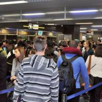 Incoming passengers wait to clear immigration procedures at Narita International Airport's Terminal 2 at the end of February. | KYODO