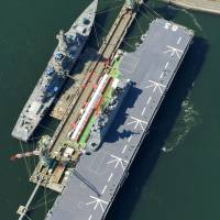 The helicopter carrier Izumo is seen from the air Wednesday in Yokohama. The ship's flight deck has fueled speculation it could be a prototype conventional aircraft carrier.   KYODO