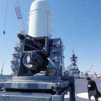 A journalist examines an anti-aircraft weapons system mounted on the flight deck of the Izumo helicopter carrier before its commissioning ceremony at a dock in Yokohama on Wednesday.   REIJI YOSHIDA