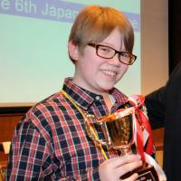 Sean Fogerty, a student attending Robert D. Edgren High School in Misawa, Aomori Prefecture, poses with his trophy after winning the 6th Japan Times Bee in Tokyo on Saturday. For the championship word, the 13-year-old correctly spelled 'snood,' a net or fabric bag for confining a woman's hair pinned or tied on at the back of the head. | SATOKO KAWASAKI