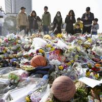 People pray and offer flowers Saturday on the banks of the Tama River in Kawasaki, where 13-year-old Ryota Uemura was fatally stabbed. | KYODO