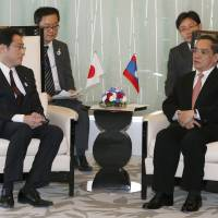 Laotian Prime Minister Thongsing Thammavong (right) talks with Foreign Minister Fumio Kishida during a meeting at a hotel in Tokyo on Wednesday. | AP