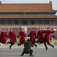 Chinese hostesses serving delegates from the National People's Congress, jump as they pose for photos in Tiananmen Square in Beijing on Thursday. | AP