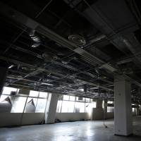 Air ducts and power lines dangle from the ceiling of a commercial building, owned by auto-parts maker Murata Spring Co., in an industrial park on the old factory site of Panasonic Corp. in Utsunomiya, Tochigi Prefecture, on Feb. 13. | BLOOMBERG