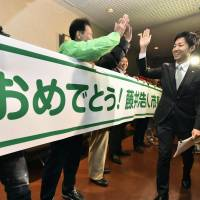 Minokamo Mayor Hiroto Fujii, the nation's youngest, smiles with supporters Thursday in Minokamo, Gifu Prefecture, after he was acquitted of bribery charges. | KYODO