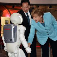 German Chancellor Angela Merkel shakes hands with Honda Motor Co.'s humanoid robot Asimo as museum head and former astronaut Mamoru Mori looks on at the National Museum of Emerging Science and Innovation in Tokyo on Monday. | AFP-JIJI