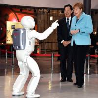 German Chancellor Angela Merkel watches a performance by Honda Motor Co.'s humanoid robot Asimo as museum head and former astronaut Mamoru Mori looks on at the National Museum of Emerging Science and Innovation in Tokyo on Monday. | AFP-JIJI