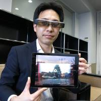 Tetsuya Kakuta, CEO of Tokyo-based AsukaLab Inc., poses with computerized glasses at his office last month while displaying a mixed reality projection of the digitally re-created donjon of Edo Castle. | KAZUAKI NAGATA
