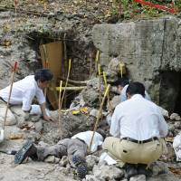 Members of a Japanese government investigation team search for the remains of Imperial army soldiers Wednesday on the island of Peleliu in Palau.   KYODO