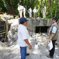 Palau President Tommy Remengesau (in vest) observes on Wednesday the work of a Japanese team searching for the remains of soldiers who died in battle on Peleliu Island, Palau. | KYODO