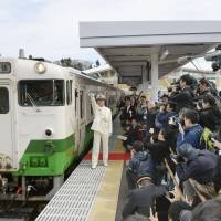 A train leaves Onagawa Station in Miyagi Prefecture on Saturday, marking the completion of the last remaining section of the JR Ishinomaki Line after it was badly damaged by the March 2011 tsunami. | KYODO