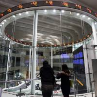 A pair of visitors observe the trading pit at the Tokyo Stock Exchange on Dec. 10. | BLOOMBERG