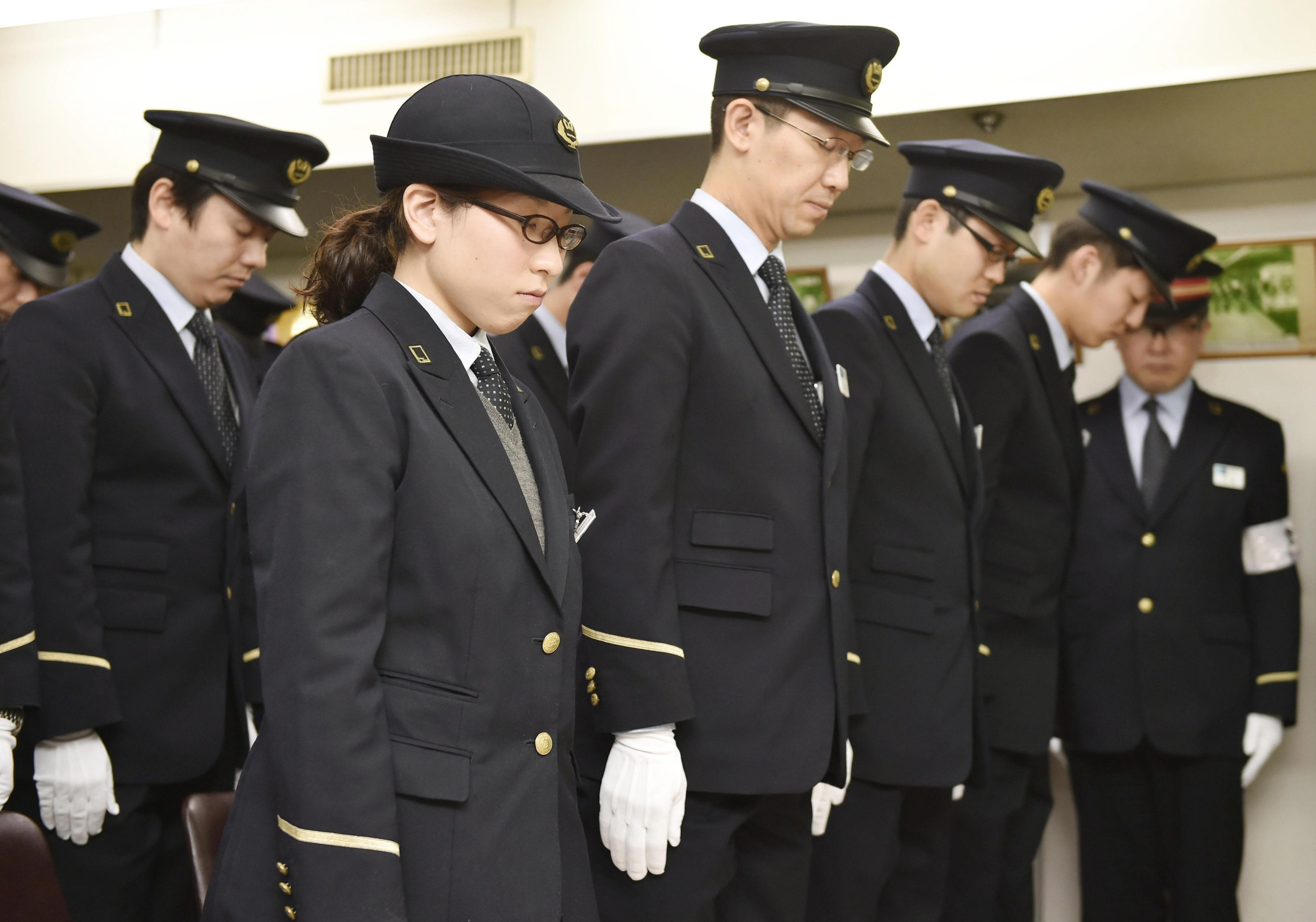 Tokyo Metro Co. staff observe a moment of silence Friday at Kasumigaseki Station to mark the 20th anniversary of the deadly sarin attack on the Tokyo subway system by doomsday cult Aum Shinrikyo. | KYODO