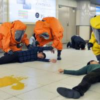 Police officers in hazmat suits conduct a sarin gas drill at JR Ikebukuro Station in Tokyo on Friday morning. | KYODO