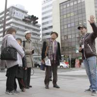 Justin Velgus (right), an American living in Sendai, guides a group of tourists around the city on March 7 ahead of the United Nations World Conference on Disaster Risk Reduction, which starts Saturday. | KYODO