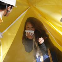 A woman emerges from a smoke tent during a disaster drill at the Roppongi Hills complex in Tokyo on Wednesday, the fourth anniversary of the 2011 earthquake and tsunami that killed thousands. | REUTERS