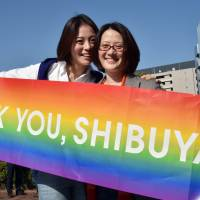 Gay couple Hiroko Masuhara (left) and Koyuki Higashi smile as the Shibuya Ward Assembly in Tokyo voted Tuesday to approve issuing 'partnership' certificates to same-sex couples. | AFP-JIJI